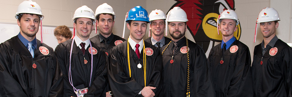 Construction Management students in commencement gowns and hardhats